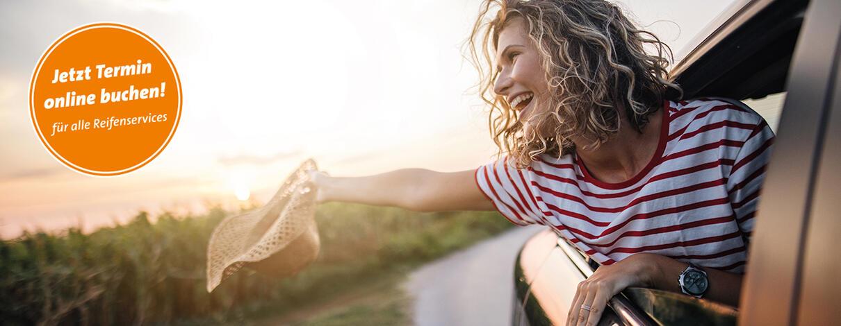 Frau mit rot-weiß gestreiftem T-shirt winkt mit einem Hut aus einem fahrenden Auto
